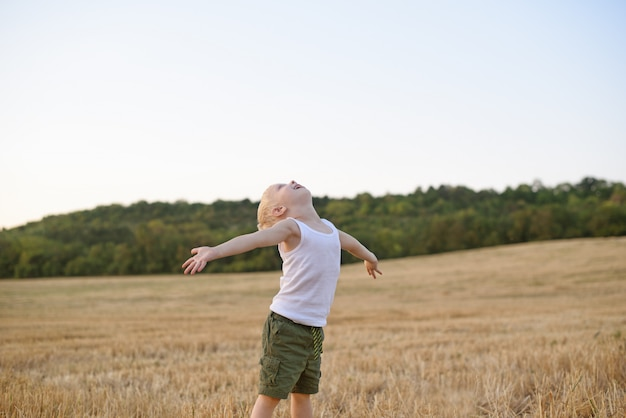 Happy blond boy stands with his arms apart and head up in a mowed wheat field
