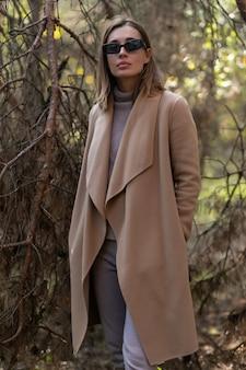 가 숲에서 산책 하는 클래식 코트에 행복 한 금발 패션 여자
