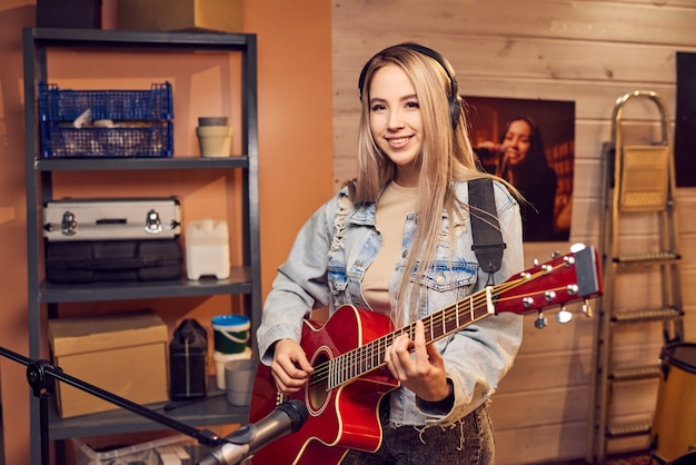 エレクトリックギターを弾くデニムジャケットの幸せなブロンドの女の子