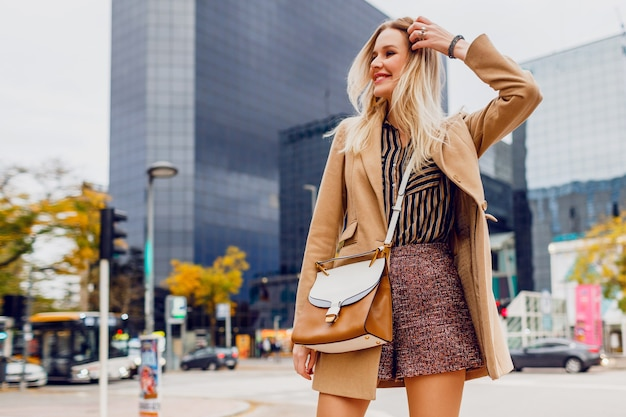 Счастливая белокурая девушка весной в повседневной одежде гуляет на открытом воздухе и наслаждается праздниками в большом современном городе. в шерстяном бежевом пальто и блузке в полоску. стильные аксессуары.