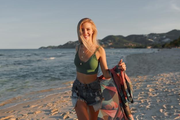 Happy blond girl running on the beach, enjoying summer.
