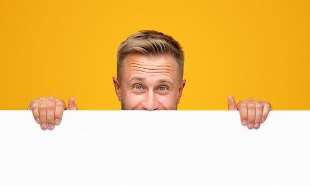 Счастливый белокурый парень смотрит в камеру и демонстрирует пустой рекламный щит