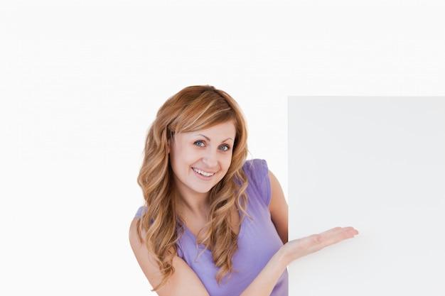 白いボードを持っている幸せなブロンドの女性