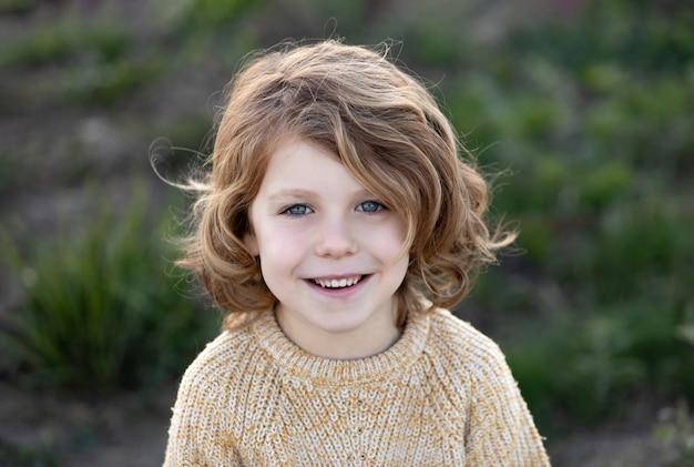 Счастливый белокурый ребенок с желтым свитером в солнечный день