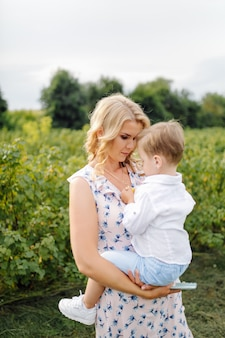 Happy blond woman and cute little boy standing in summer garden