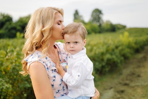 Happy blond woman and cute little boy standing in summer garden