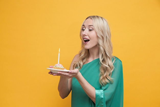 Happy blond woman holding cake with candles, making wish, celebrating birthday on yellow