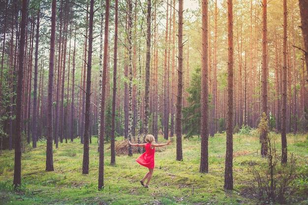 소나무 숲에서 춤을 추는 빨간 드레스에 행복 한 금발 여자