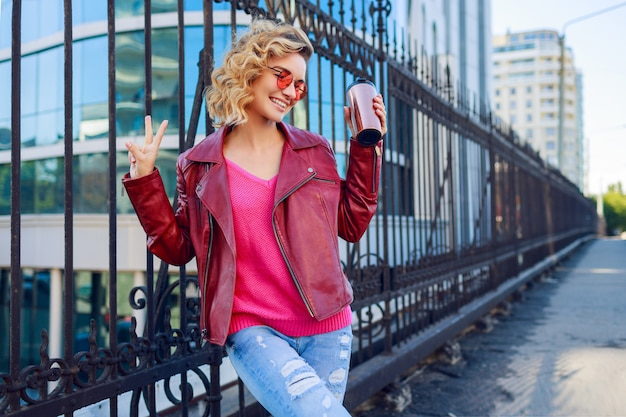 Happy blond woman posing on modern streets, drinking coffee or cappuccino. stylish autumn outfit, leather jacket and knitted sweater. pink sunglasses.
