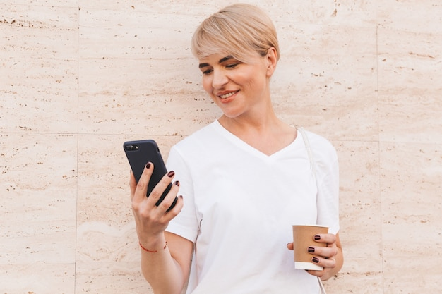 Happy blond woman wearing white t-shirt using mobile phone, while standing against beige wall outdoor in summer and drinking coffee from paper cup