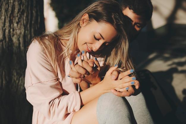 Счастливая белокурая женщина с мужчиной, сидящим возле дерева в солнечном свете и обнимающимся с любовью