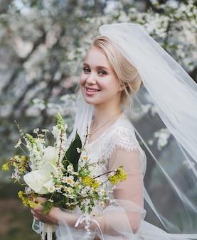 幸せな金髪の花嫁は、新郎を待っている彼女の手で結婚式の花束を持って微笑む