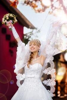 手にウェディングブーケと幸せな金髪の花嫁