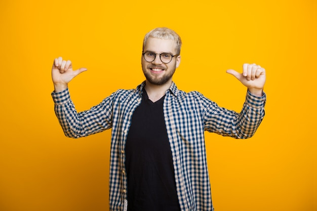 Happy blonde caucasian man pointing at him wearing eyeglasses and beard on a yellow