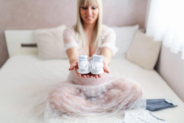 足を組んでベッドに座って赤ちゃんの靴を保持している幸せな金髪白人女性。寝室のインテリア。