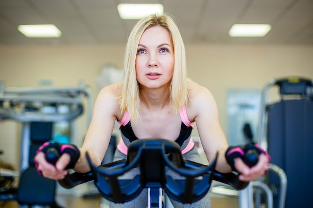 Happy blonde doing indoor biking in a fitness club
