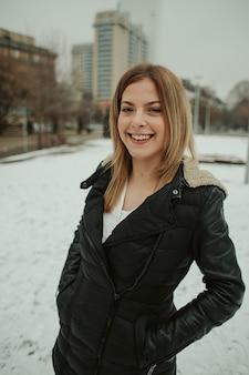 屋外のダウンジャケットで幸せな金髪の女性