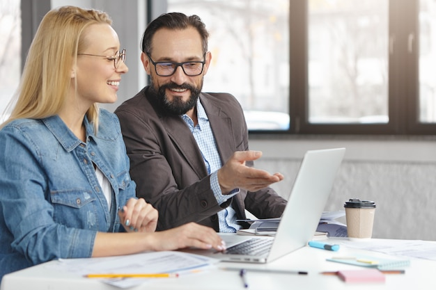 Happy blonde female manager has conversation with male colleague