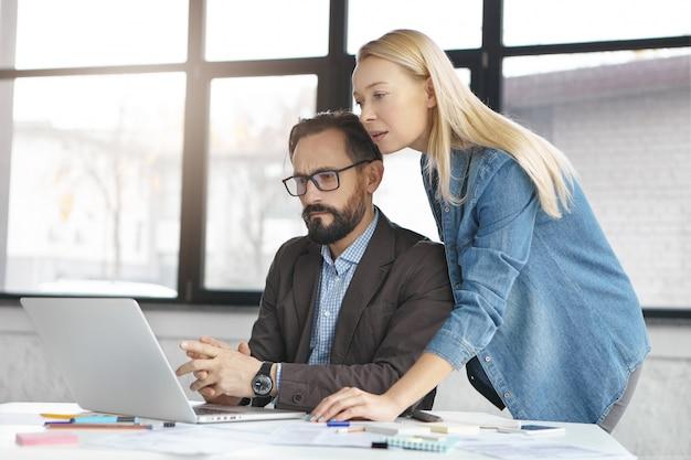 幸せな金髪女性マネージャーは男性の同僚との会話をしています