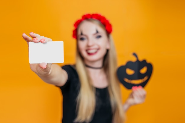 Happy blonde girl in halloween costume shows white credit card isolated on orange