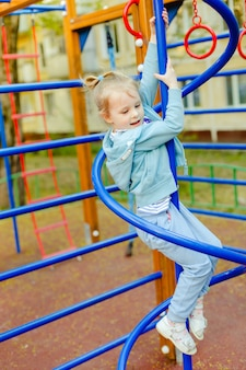 Happy blonde girl having fun on a playground enjoying in climbing on a summer day in a sunny city park.