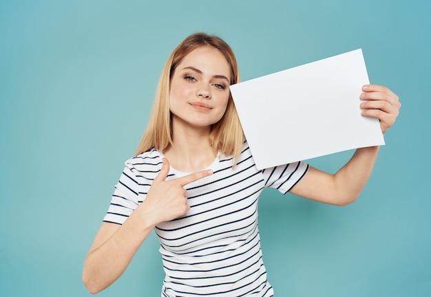 Счастливая блондинка в полосатой футболке баннер белый лист бумаги макет