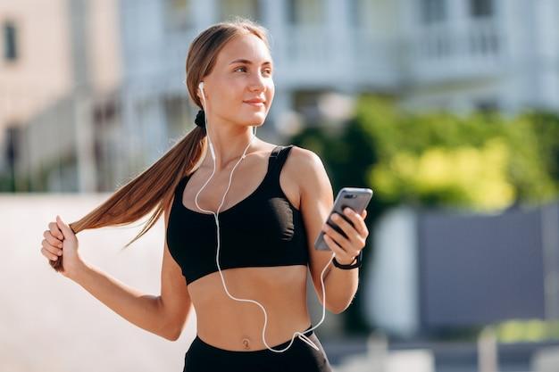 Happy blonde girl  wearing in sportswear in earphones holding a smartphone.