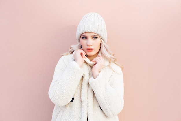 Happy blonde girl in white winter clothes posing against a pink wall.