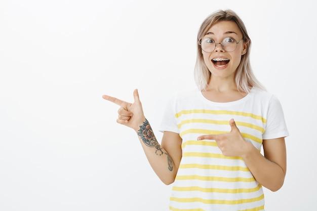 スタジオでポーズをとってメガネで幸せなブロンドの女の子