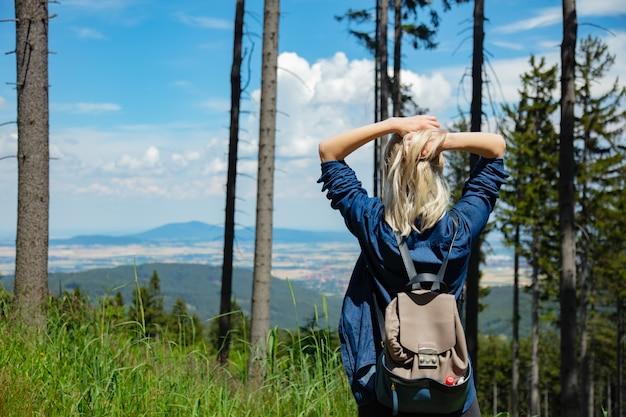Счастливая белокурая девушка с packpack в горы.