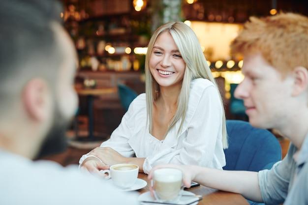 授業後にカフェのテーブルで2人の男とチャットしながらカプチーノのカップを持っている歯を見せる笑顔で幸せなブロンドの女の子