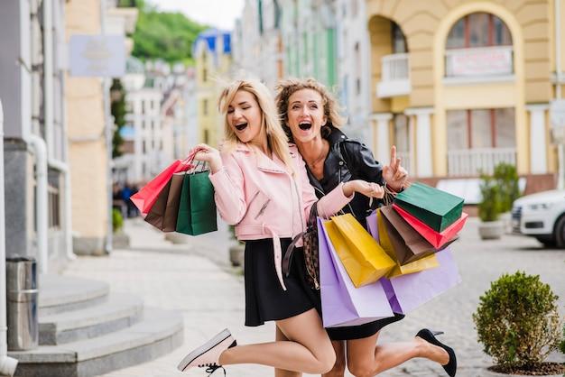 Happy blonde girls standing holding bags hugging