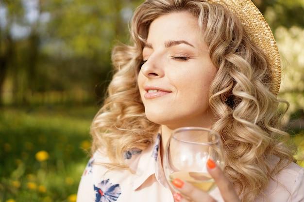 夏の日の緑豊かな公園で日没時のピクニック中に白ワインのグラスを保持している幸せなブロンド