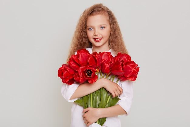 Счастливый белокурый ребенок с волнистыми волосами, смотрящий вперед со счастливым выражением лица, держащий красные тюльпаны, рад получить красивые цветы