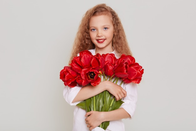 Happy blonde kid with wavy hair looking at front with happy expression, holding red tulips, being glad to get beautiful flowers