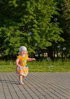 Happy blonde little girl in the summer having fun with soap bubbles outdoors