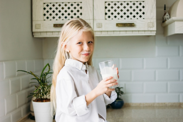 Happy blonde long hair little girl drinking milk in kitchen, healthy lifestyle