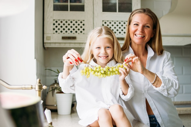 Happy blonde long hair mom and daughter having fun with grapes in kitchen, healthy family lifestyle