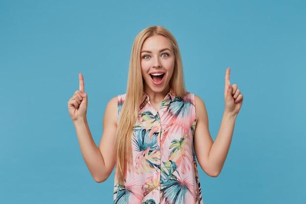 낭만적 인 드레스를 입고 캐주얼 헤어 스타일을 가진 행복한 금발의 긴 머리 여성, 포즈를 취하는 동안 집게 손가락으로 위쪽으로 표시, 넓게 미소 짓기