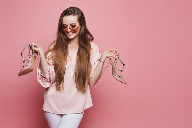 Happy blonde model girl with a shiny smile in beige blouse and in fashionable pink sunglasses holding stylish shoes in her hands and posing at the pink background, isolated