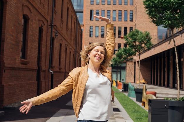 街の通りで幸せな金髪のポーズをとって、彼女の幸せな観光と喜びのブログを共有しています...