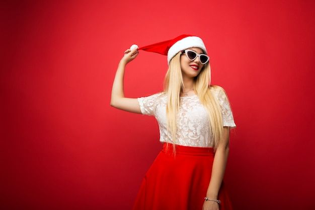 Happy blonde in santa hat on red isolated background. white rimmed sunglasses.