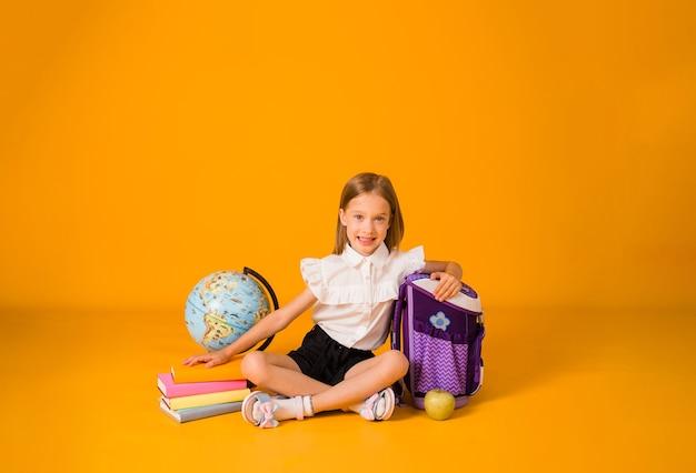 Счастливая блондинка школьница в форме сидит со школьными принадлежностями на желтом фоне с копией пространства