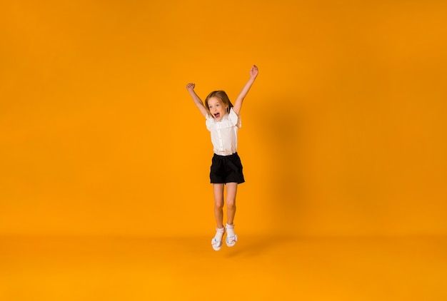 제복을 입은 행복한 금발 여학생이 노란색 배경에 공간 사본을 들고 뛰어다닌다