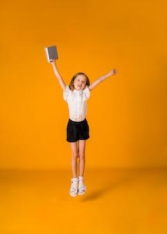 제복을 입은 행복한 금발 여학생이 노란색 배경에 파란색 메모장을 들고 공간 사본을 들고 점프합니다.