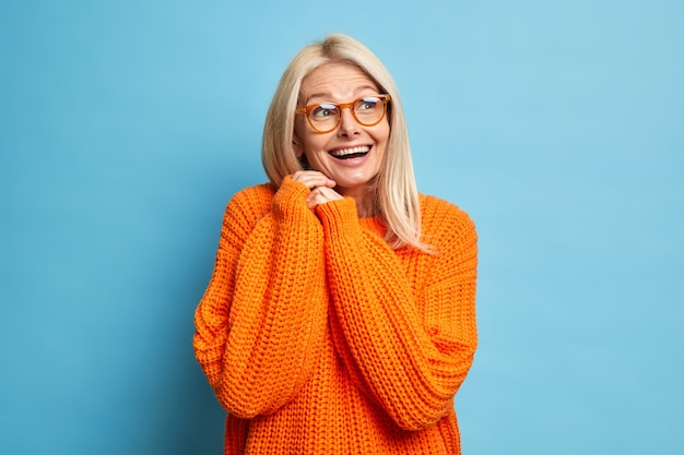 Happy blonde senior european woman recalls something pleasant laughs happily and keeps hands pressed together wears optical glasses loose knitted orange jumper.