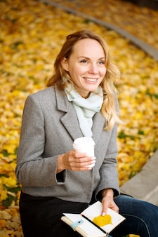 Happy blonde  smiling woman with paper notebook and coffee drink outdoors in autumn park