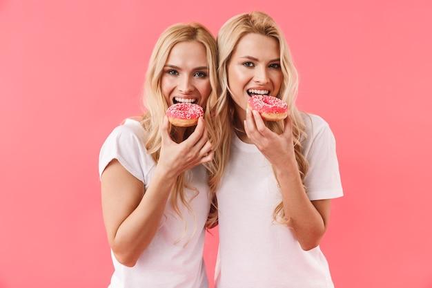 Счастливые белокурые близнецы в футболках едят пончики и смотрят спереди через розовую стену