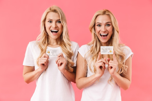 Happy blonde twins wearing in t-shirts holding credit cards and looking at the front over pink wall