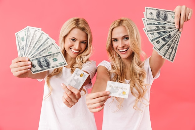 Happy blonde twins wearing in t-shirts showing money and credit cards at front over pink wall